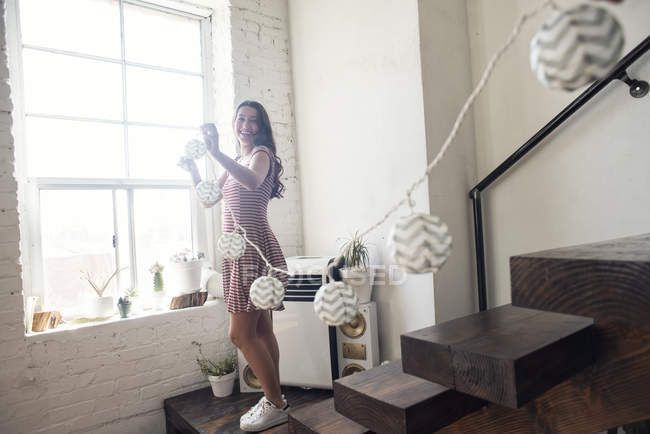 Young woman decorating loft with fairylights — Stock Photo