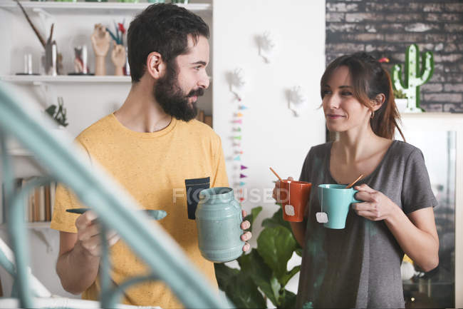Junge Frau bringt zwei Tassen Tee während Freund Malerei Sessel — Stockfoto