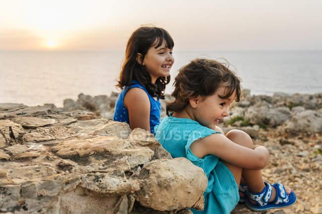 Two happy little girls enjoying sunset near sea — Stock Photo