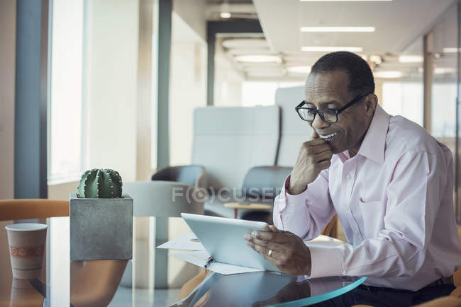 Businessman working alone in office with digital tablet — Stock Photo