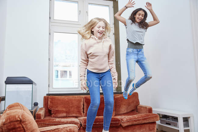 Due ragazze felici saltando e ballando a casa — Foto stock