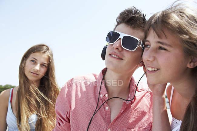 Three teenage friends with headphones outdoors — Stock Photo