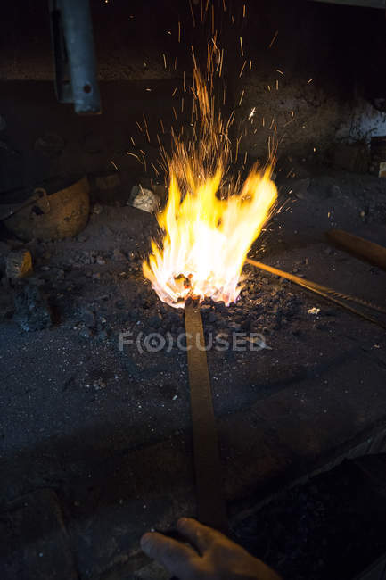 Blacksmith hands with metal detail by the fire — Stock Photo