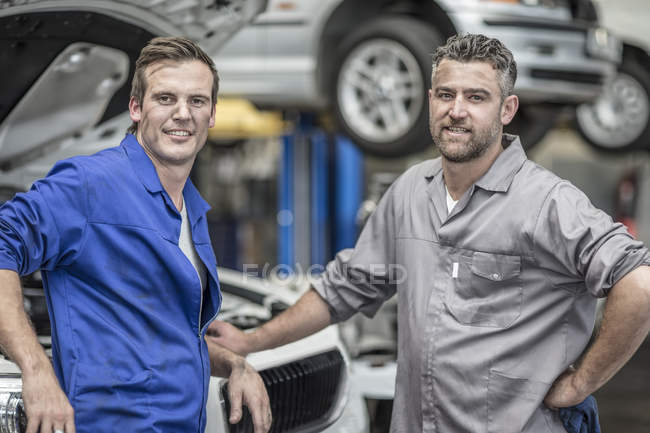 Two confident car mechanics in repair garage — Stock Photo