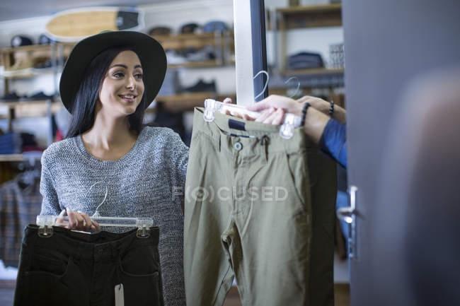 Mujer trae pantalones para amigo para probarse - foto de stock