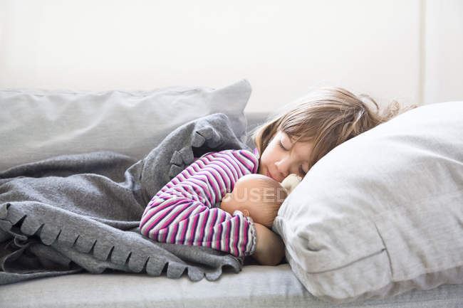 Little girl sleeping on couch with doll stock photo 173588384 - Dormire sul divano ...