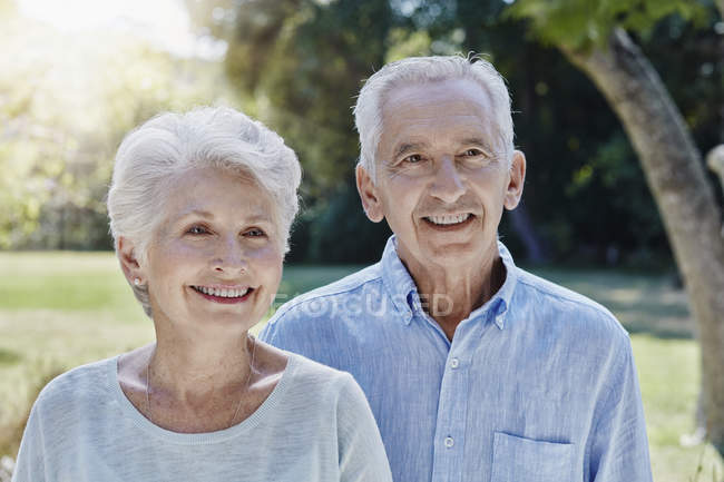 Portrait of smiling senior couple in park — Stock Photo
