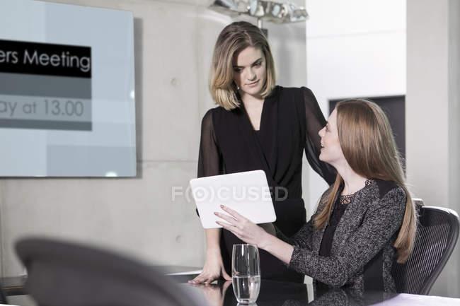 Mulheres de negócios em reunião discutindo no escritório, usando o tablet digital — Fotografia de Stock