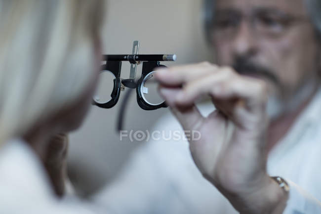 Optometrist adjusting test frame for patient in medical clinic — Stock Photo