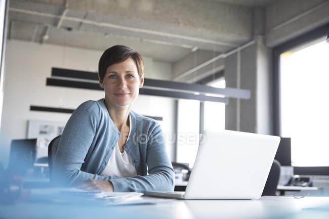 Портрет усміхнений підприємець, сидячи в офісі з ноутбуком — стокове фото