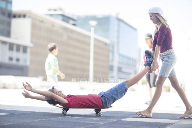 Happy kids having fun with skateboard on street — Stock Photo
