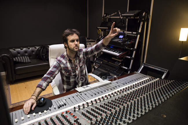 Man working in the control room of a recording studio raising his hand — Stock Photo