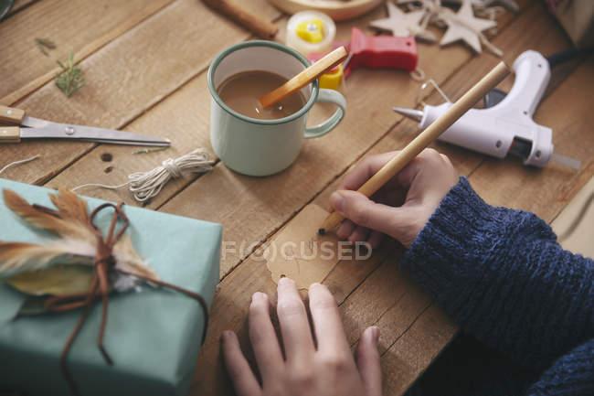 Frau schreibt auf Weihnachtsgeschenkanhänger, Nahaufnahme — Stockfoto