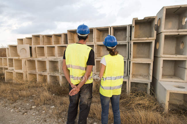 Man and woman in safety vestslooking at  concrete structures — Stock Photo
