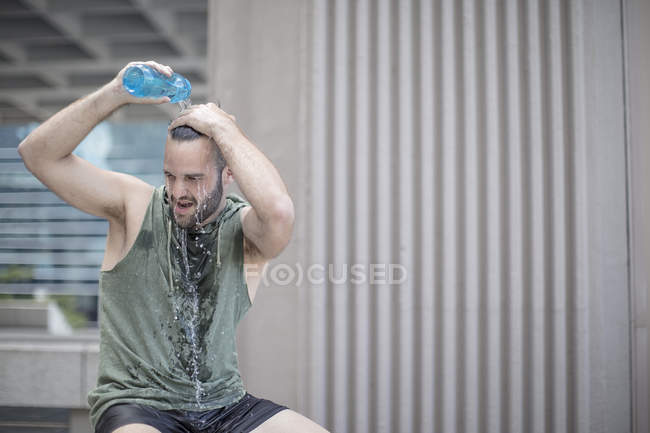 Athlete taking a break pouring water over his head — Stock Photo
