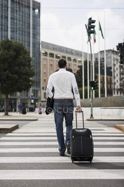 Back view of businessman with suitcase crossing the street — Stock Photo