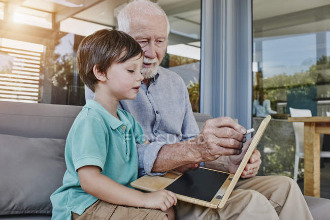 Portrait of senior man with grandson using chalkboard — Stock Photo