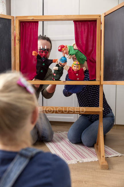 Happy little girl watching Punch and Judy show played by her parents — Stock Photo