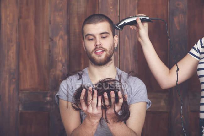 Ritratto di giovane uomo che si fa tagliare i capelli dalla sua ragazza con la macchina per tagliare i capelli — Foto stock