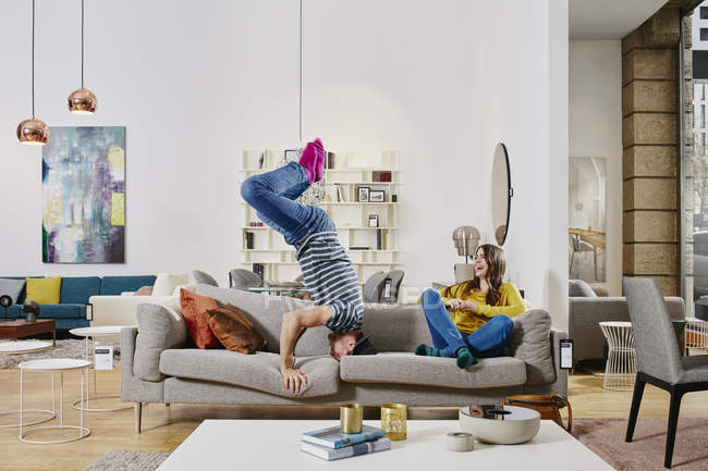 Portrait of couple having fun on sofa in furniture store — Stock Photo