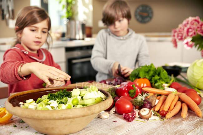 Menino e menina para legumes na cozinha — Fotografia de Stock