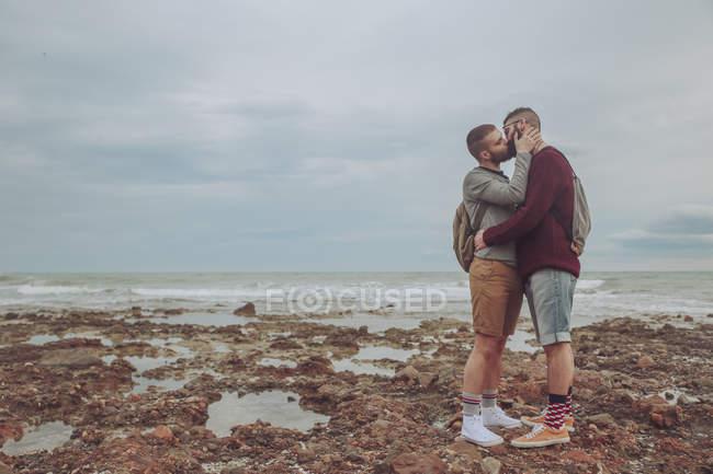Молодой гей-пара целоваться на пляже — стоковое фото