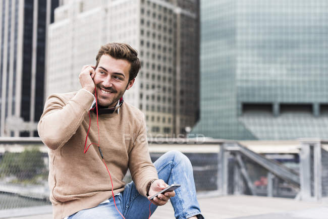 Businessman sitting in Manhattan and using smartphone and earphones, New York City, USA — Stock Photo