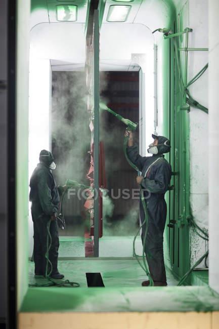 Художники обприскування компонентів стали в Бут Спрей заводу — стокове фото