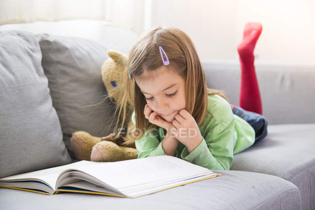 Little girl lying on couch and reading book — Stock Photo