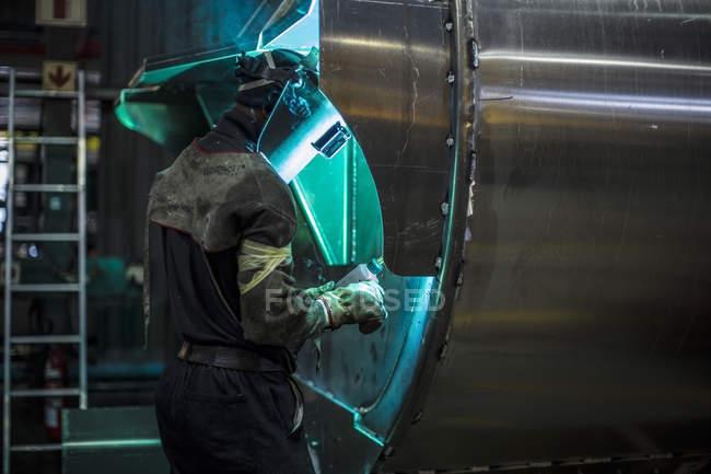 Человек сварочный стальной бак на заводе — стоковое фото