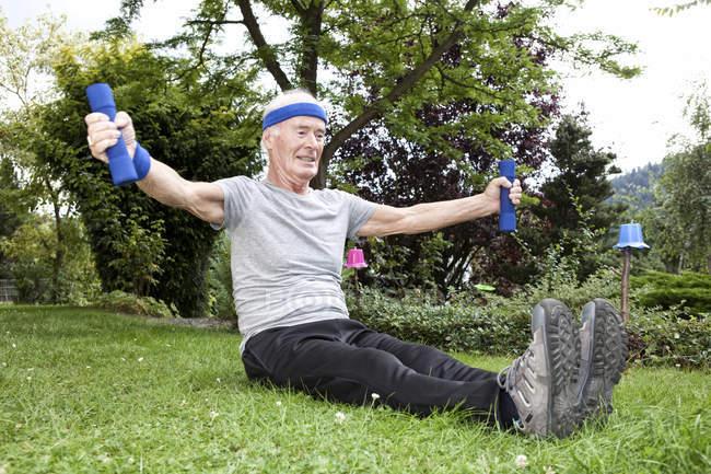 Senior man doing fitness training with dumbells in garden — Stock Photo