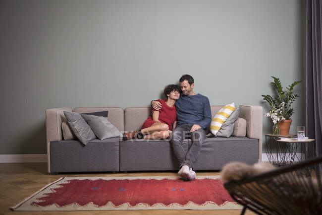 Couple sitting together on the couch in modern apartment — Stock Photo