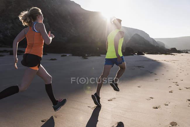 Jeune couple courant sur la plage, france, péninsule de crozon — Photo de stock