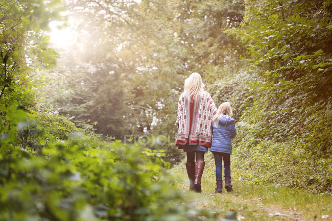 Back view of mother and little daughter walking in autumnal forest — Stock Photo