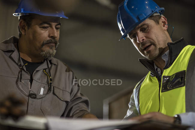 Engineers discussing construction plans at workshop — Stock Photo