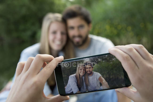 Cell phone picture of smiling young couple at a lake — Stock Photo