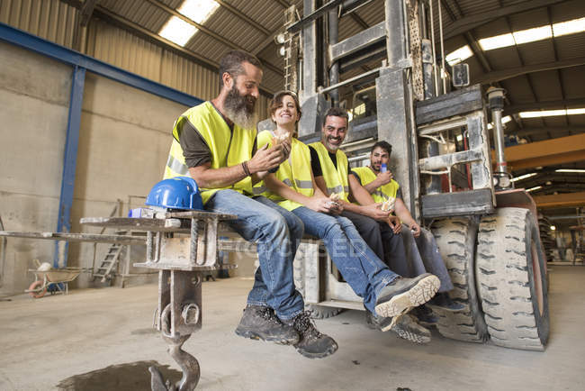 Workers having lunch on the shovel of a giant forklift — Stock Photo