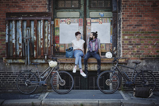 Portrait of couple resting on building near bicycles — Stock Photo