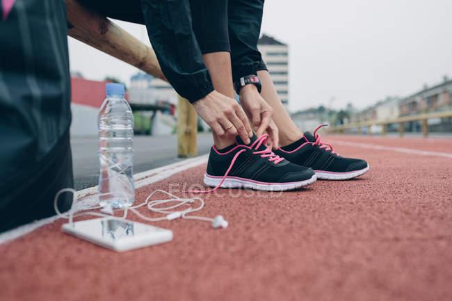 Femme sur la piste de tartan attachant chaussures — Photo de stock