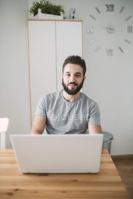 Portrait of young man using laptop at home — Stock Photo