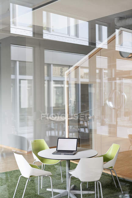Modern office interior with laptop on the table — Stock Photo