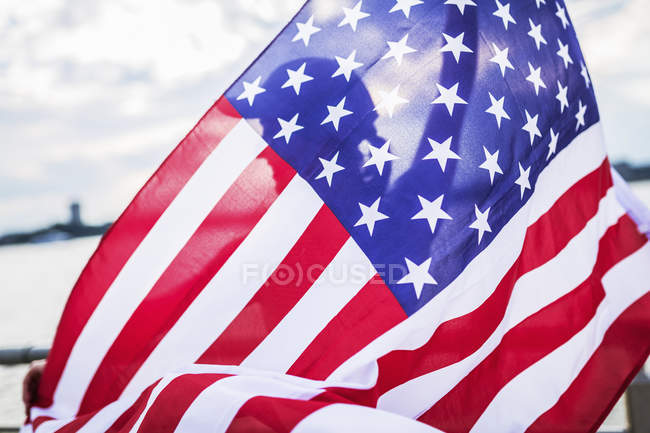 Silhouette of woman behind American flag — Stock Photo