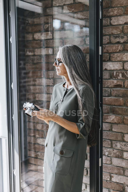 Woman with long grey hair holding camera with brick wall on background — Stock Photo
