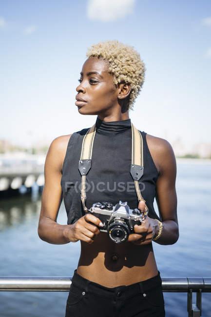 Молодая африканская женщина с камерой на набережной смотрит вокруг — стоковое фото