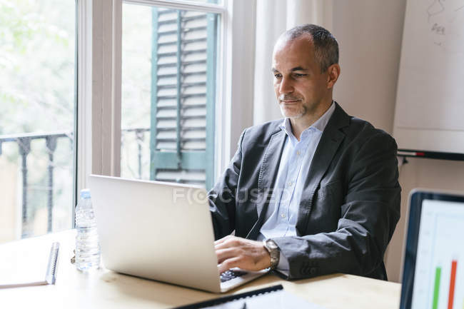 Businessman sitting at desk and working on laptop — Stock Photo