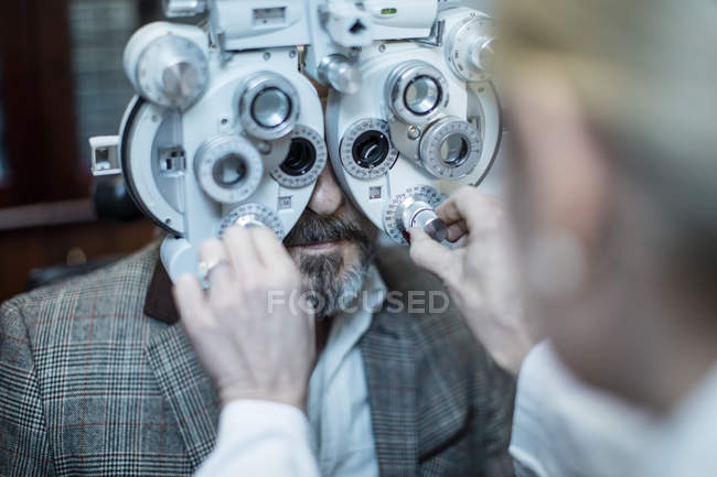 Female optometrist doing eye test with patient in medical clinic — Stock Photo