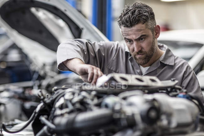 Car mechanic in a workshop working on engine — Stock Photo