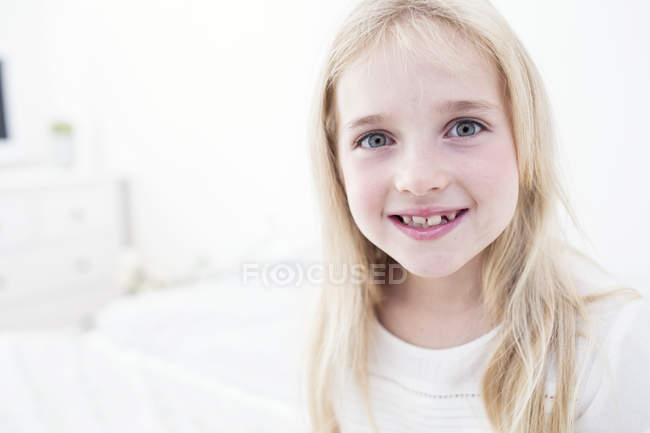 Portrait of smiling blond girl looking at camera — Stock Photo