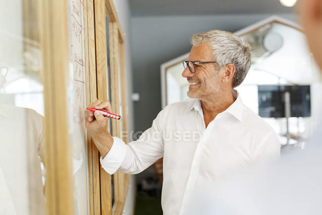 Businessman writing on board — Stock Photo