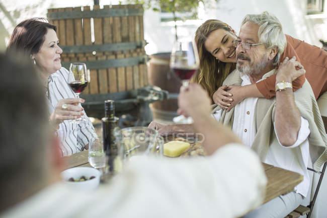 Женщина обнимает своего отца за семейным обедом, с вином и закусками — стоковое фото